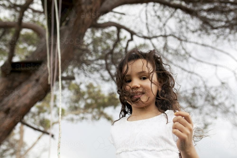 Portrait of young girl playing outside under a tree - Australian Stock Image