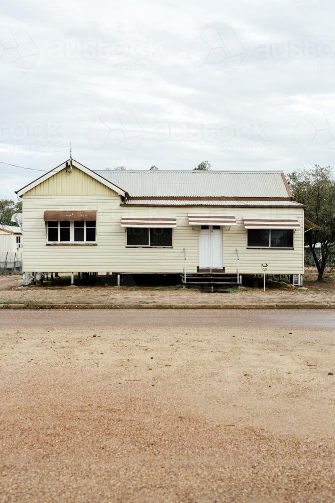 Portrait photo of cream coloured Queenslander House with brown trimming - Australian Stock Image