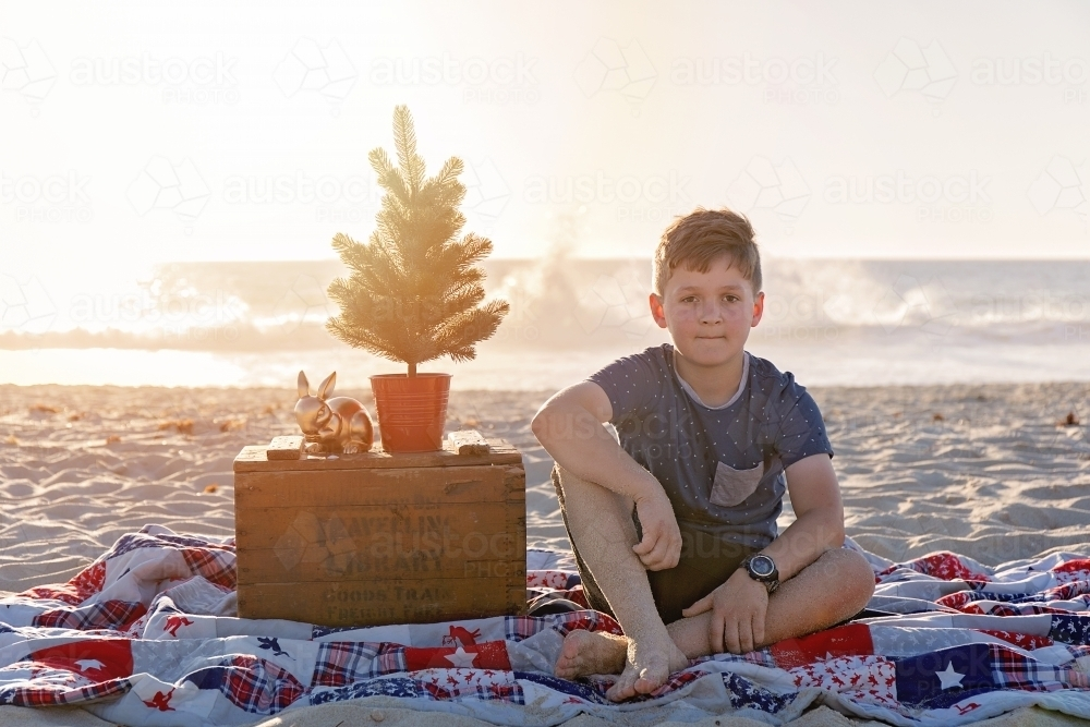 Pre Teen Boy Sitting In a Christmas Themed Setting At The Beach At Sunset - Australian Stock Image