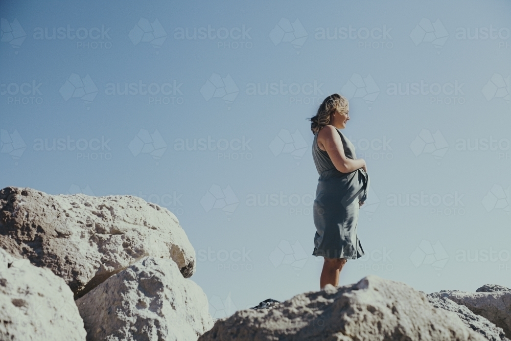 Pregnant woman looking out on the edge of a coastal cliff - Australian Stock Image