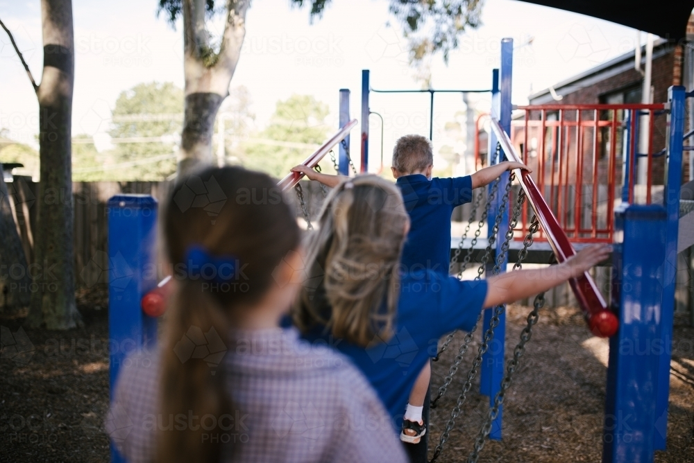 Primary school students in uniform playing at playground - Australian Stock Image