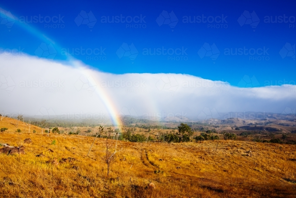 Rainbow and cloud over a rural property in the Scenic Rim - Australian Stock Image