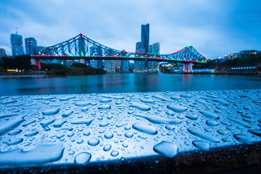 Raindrops on a metal railing with the Story Bridge in the background - Australian Stock Image
