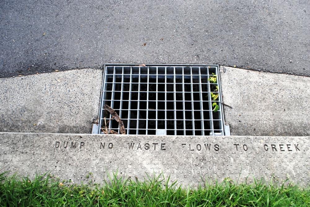 Rainwater drain on the kerb of a street in a Brisbane suburb - Australian Stock Image