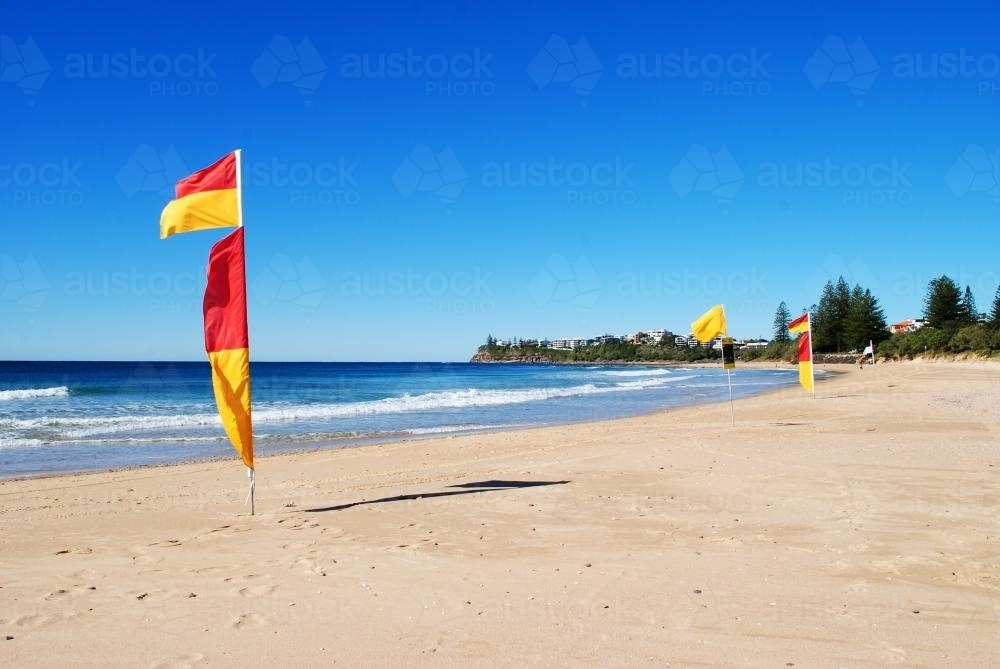 Red and yellow flags at Dicky Beach on a sunny day in winter - Australian Stock Image