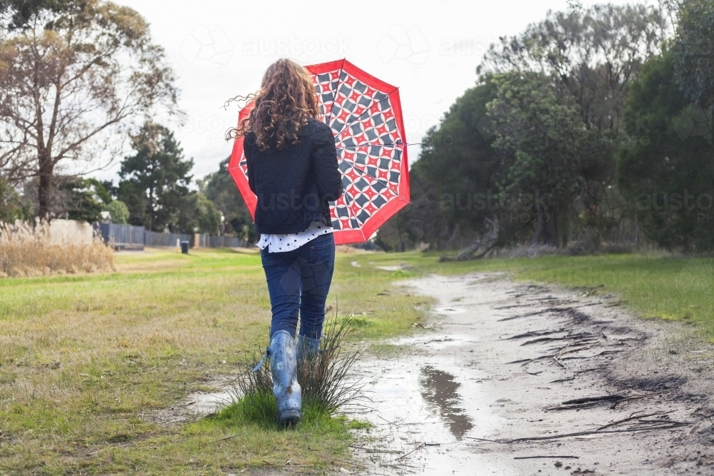 Red haired girl splashing in puddles in gumboots on a rainy winter day. - Australian Stock Image