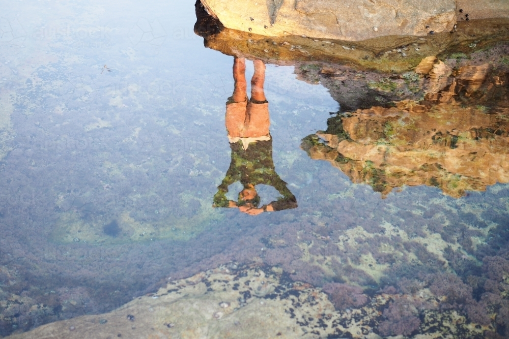 Reflection of a man in rockpool - Australian Stock Image