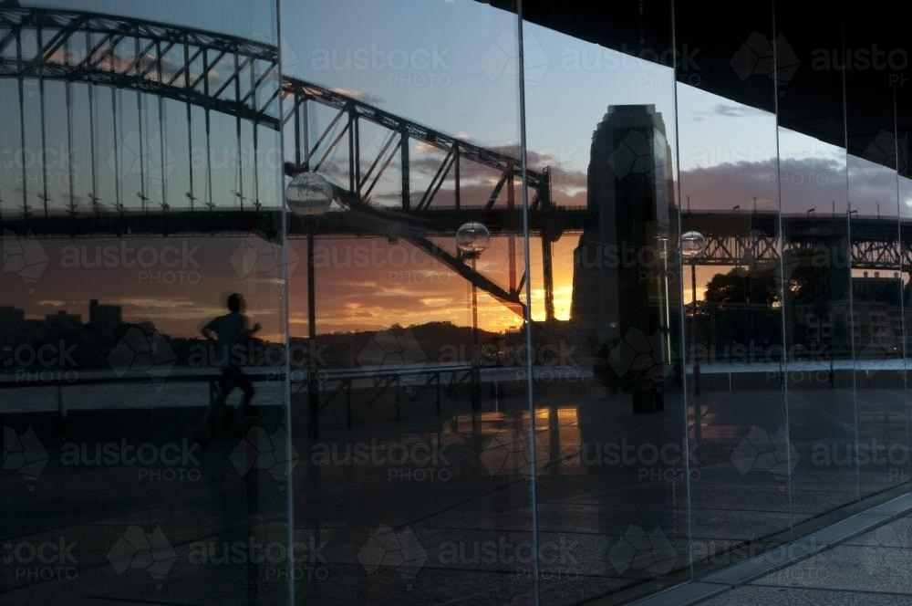Reflection of a runner and the Harbour Bridge in Opera House windows - Australian Stock Image