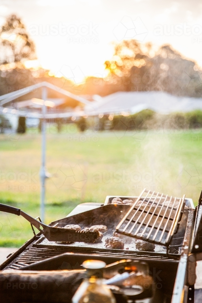 Rissoles cooking on a BBQ in the backyard at sunset - Australian Stock Image
