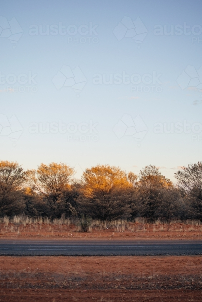 Road against a red dirt landscape - Australian Stock Image