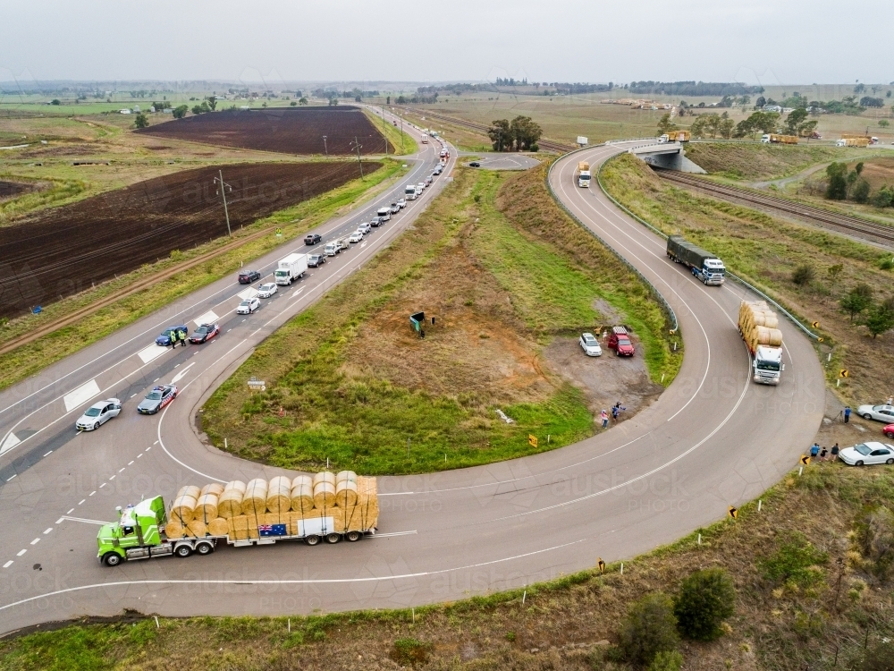 Road trains pulling out onto highway to continue journey delivering hay for drought relief - Australian Stock Image