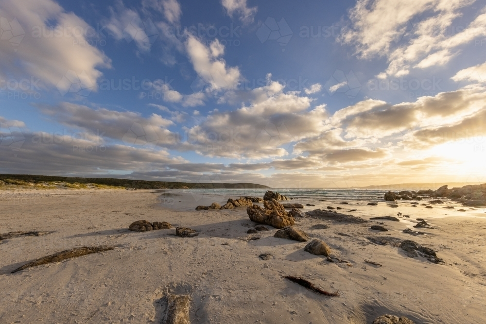rock strewn shore of south coast beach with clouds in sky - Australian Stock Image