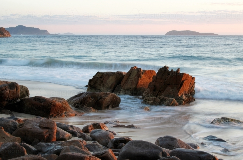 Rocks at the end of the ocean at sunrise - Australian Stock Image
