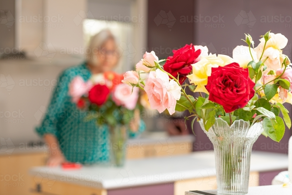 roses in vase with lady in background behind - Australian Stock Image