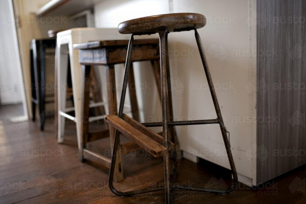 Row of miss matched stools at kitchen counter - Australian Stock Image