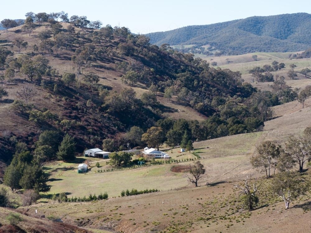 Rural homestead in a valley in hilly grazing farmland - Australian Stock Image