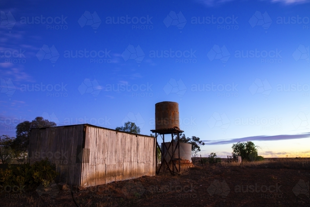 rusty old shed and tank at twilight - Australian Stock Image
