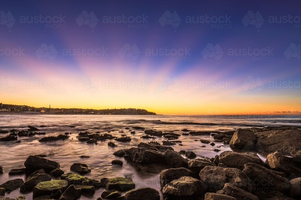 Scenic view of sea against blue sky on rocky coastline - Australian Stock Image