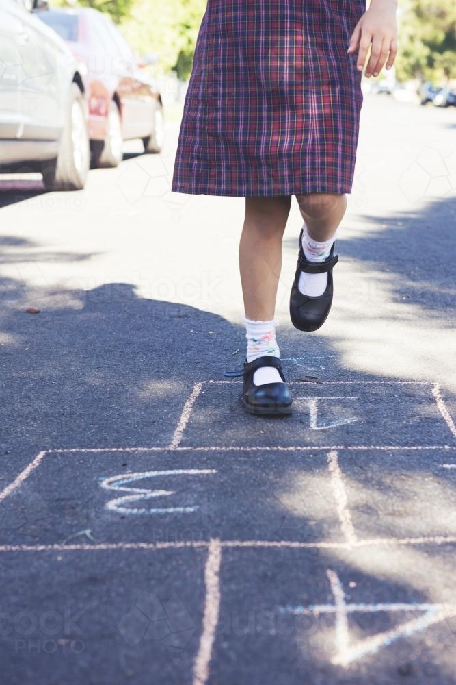 School girl playing hopscotch in the street - Australian Stock Image