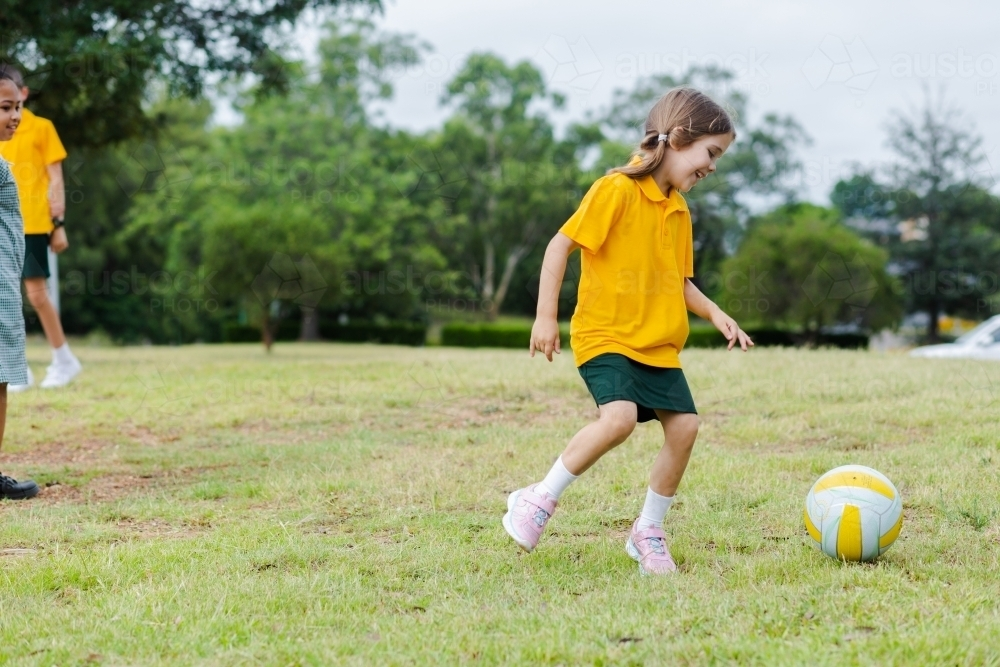 School girl playing sports with ball on grass - Australian Stock Image