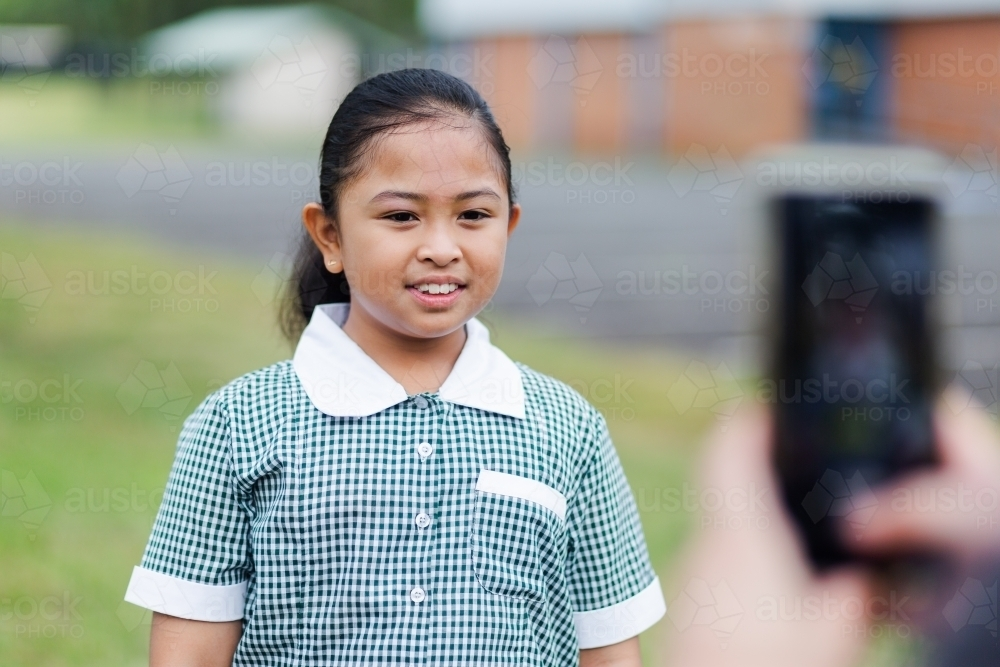 School girl standing for her mum to take her photo on her first day back to school - Australian Stock Image