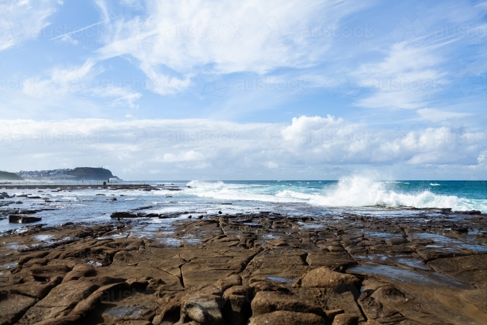 Seaside scene at Merewether looking along rocks to the ocean - Australian Stock Image