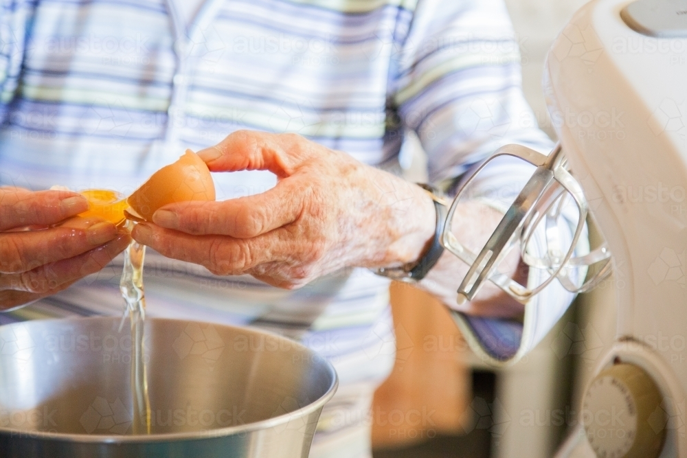 Senior citizen cooking a cake in the kitchen, cracking eggs into a bowl - Australian Stock Image