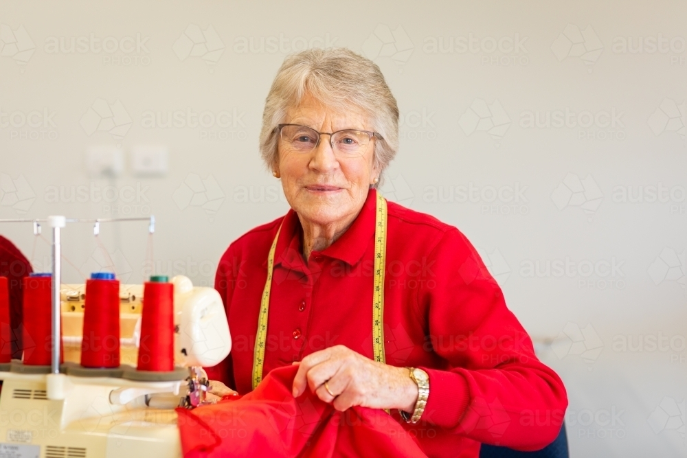 senior lady looking at camera with red fabric and overlocker machine - Australian Stock Image