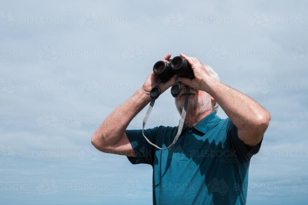 Senior looking through binoculars - Australian Stock Image