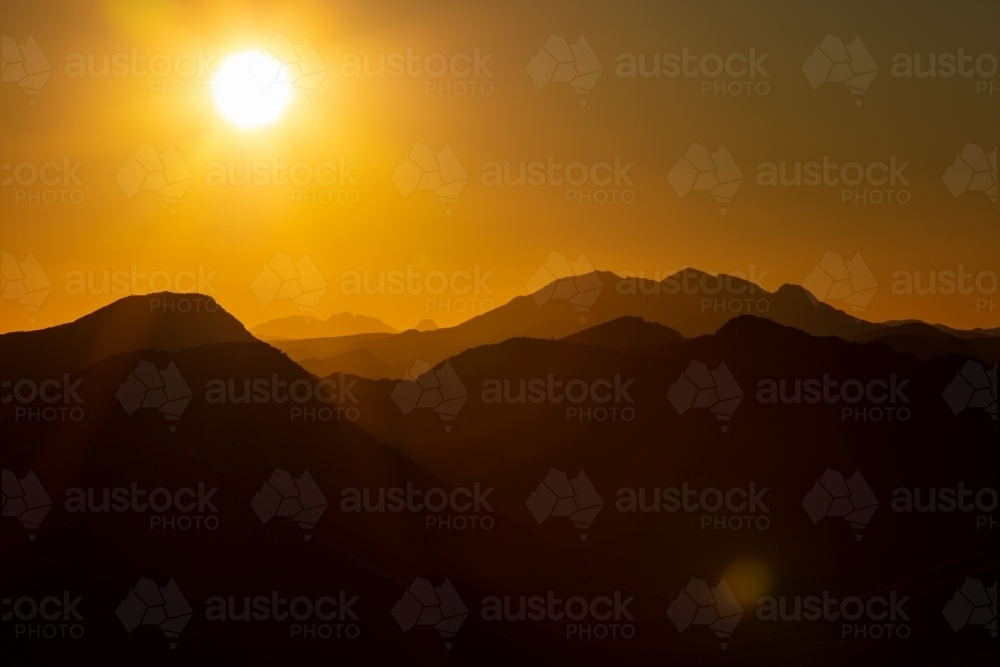 Setting sun above Mt Sonder and the West MacDonnell Ranges. - Australian Stock Image