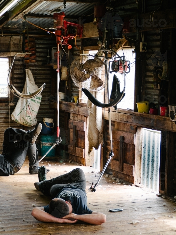 Shearers resting on shed floor at smoko time - Australian Stock Image