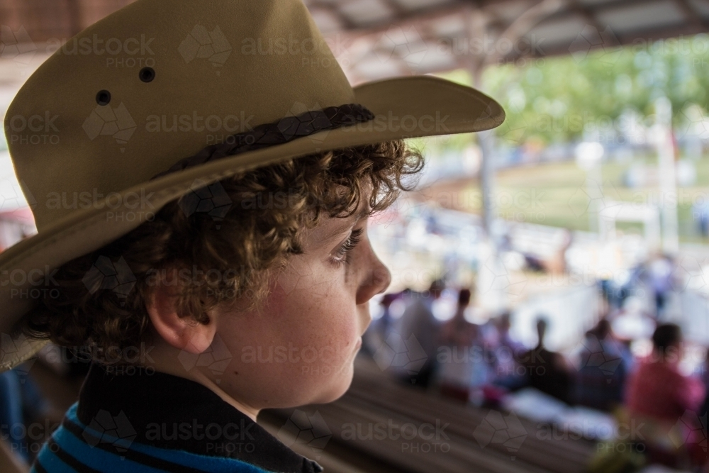 Image of Side profile of boy with curly hair sitting in