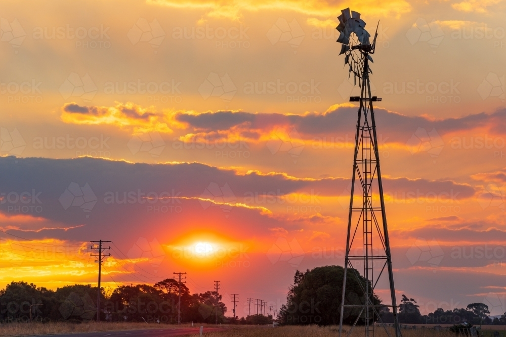 Silhouette of a farm windmill against a smokey sunset sky - Australian Stock Image