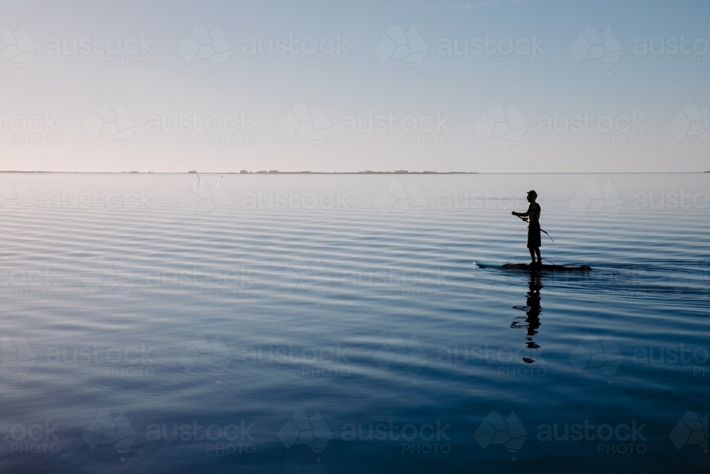Silhouette of a man on a stand-up paddle board on very still water - Australian Stock Image