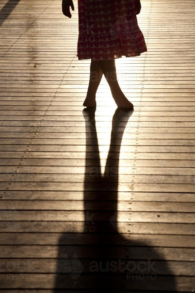 silhouette of a young girl standing on a sunlit deck with crossed legs - Australian Stock Image