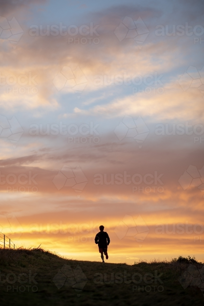 Silhouette of Man in Distance Running at Sunrise - Australian Stock Image