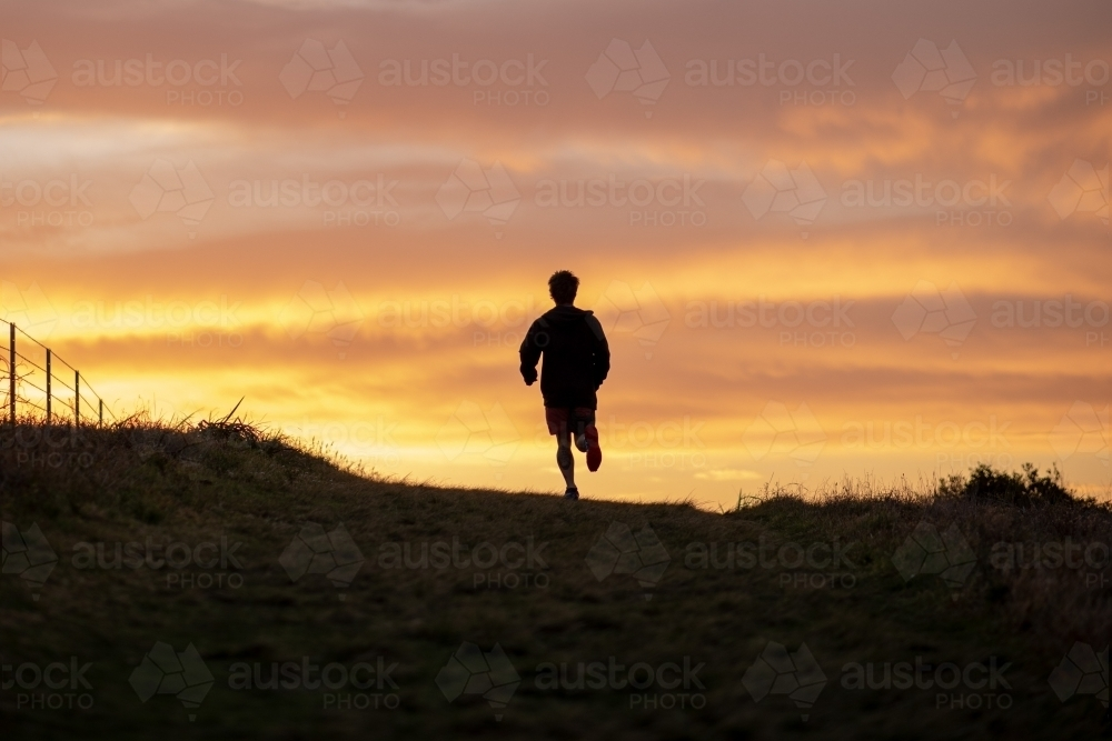 Silhouette of Man Running at Sunrise - Australian Stock Image