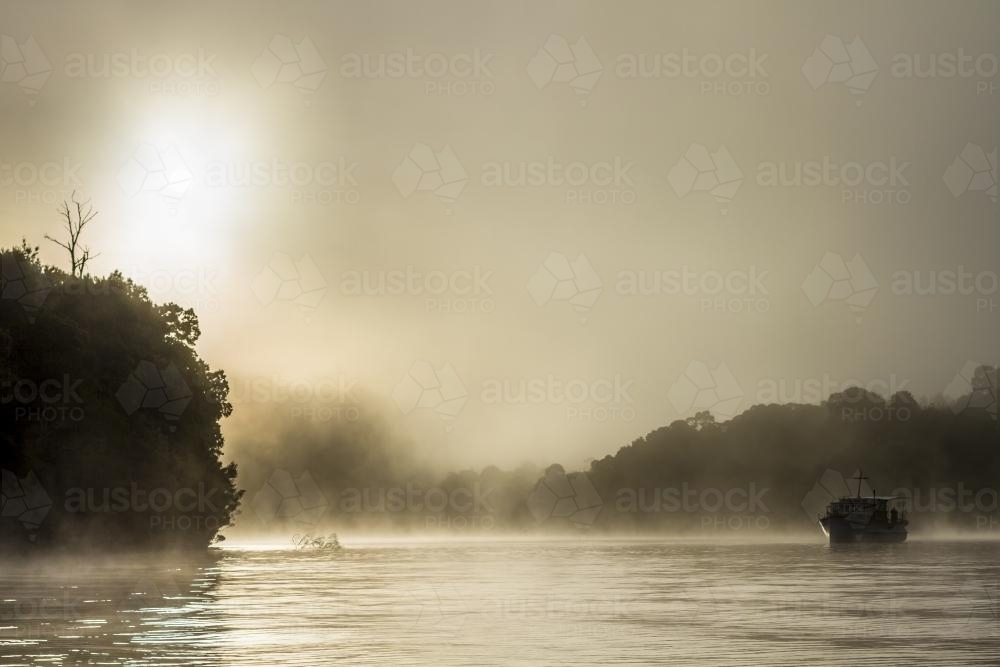 Silhouette of old wooden boat on the water in fog - Australian Stock Image