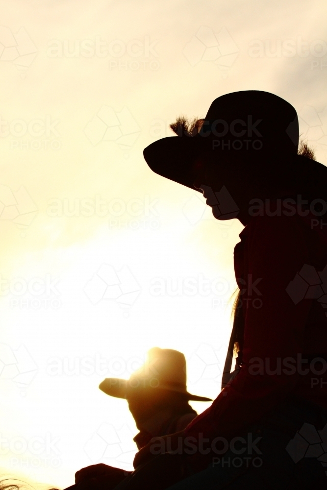 Silhouette of two country girls in their twenties, as they ride their horses - Australian Stock Image
