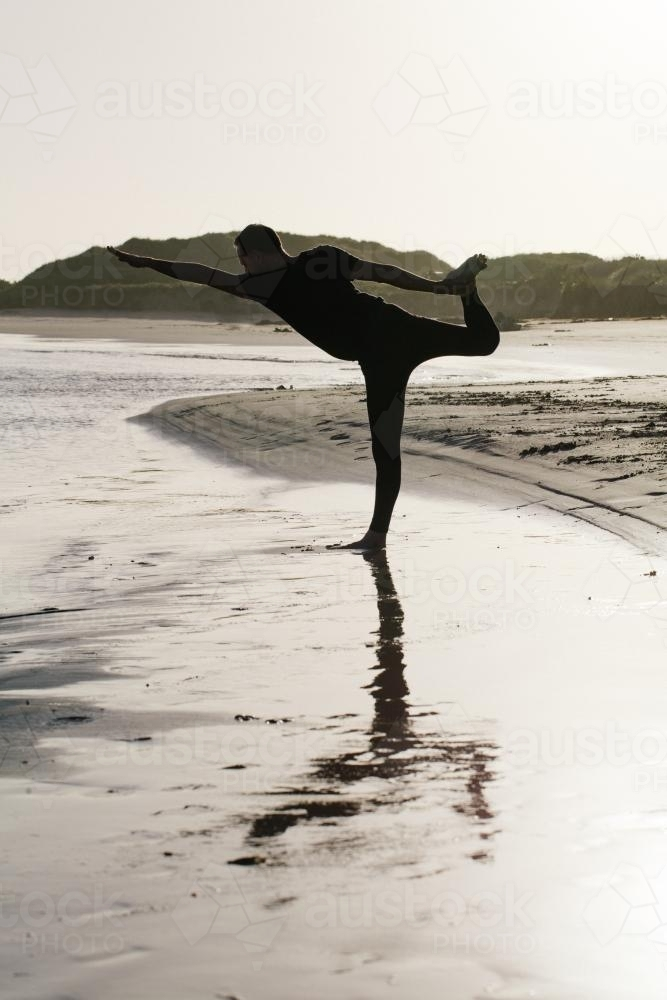 Silouette of a man doing yoga position on beach - Australian Stock Image