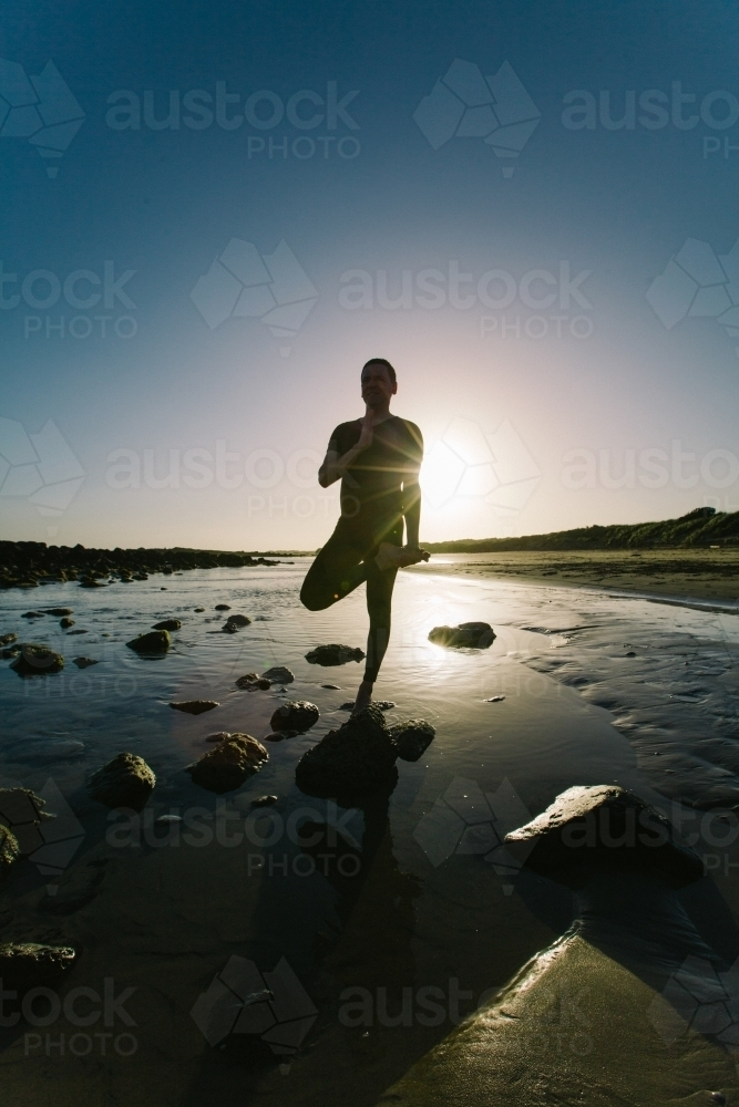 Silouette of man doing yoga poses on beach at sunset - Australian Stock Image