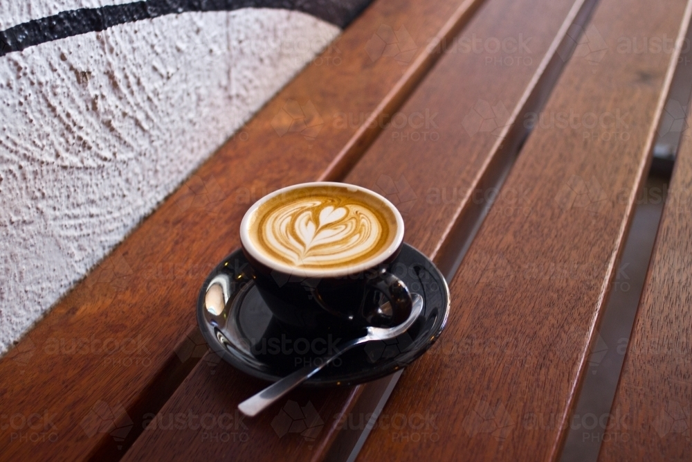 Single flat white coffee sitting on a wooden table - Australian Stock Image