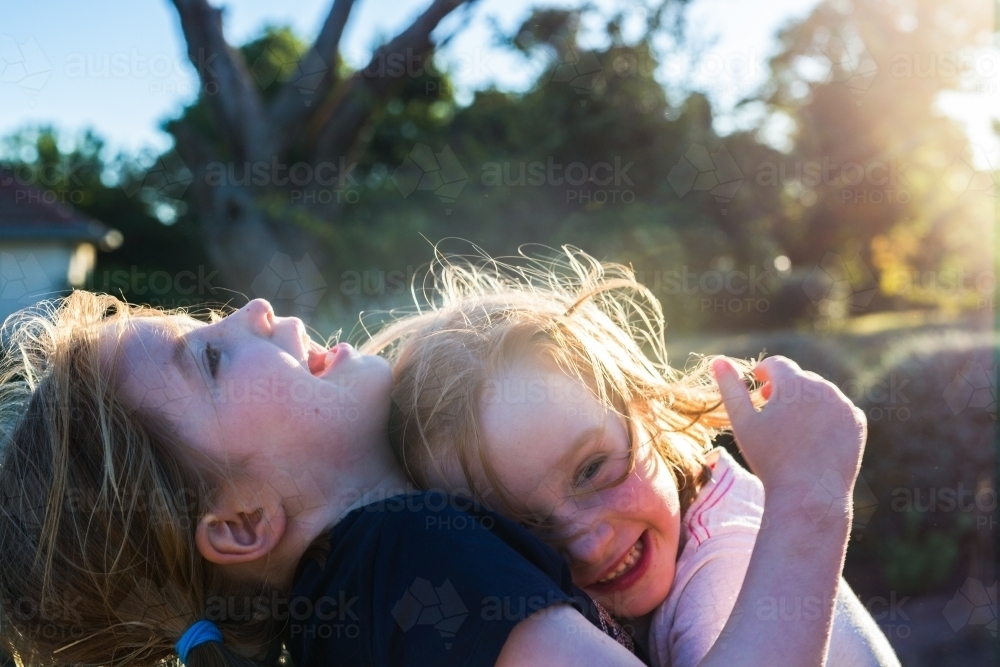 Sisters hugging in the sunshine - Australian Stock Image