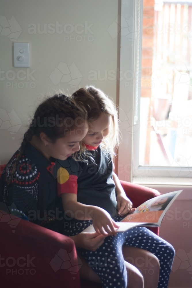 Sisters reading together - Australian Stock Image