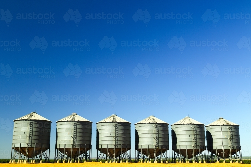 Six grain silos side by side on a farm near Breeza on the Liverpool Plains, New South Wales. - Australian Stock Image