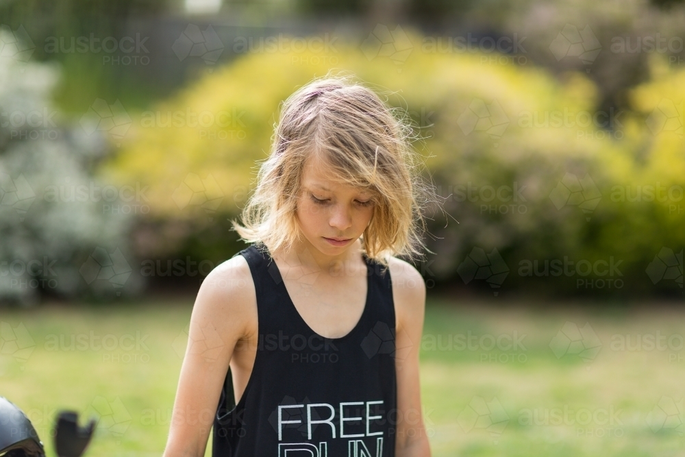 Skinny kid with scruffy hair and black singlet looking down - Australian Stock Image