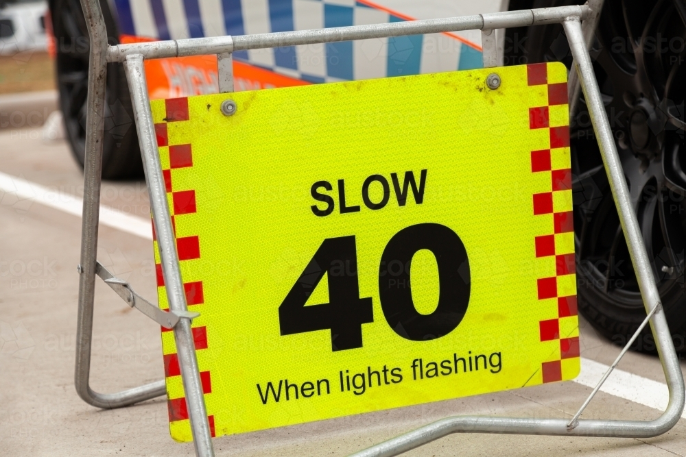 Slow 40 when lights flashing sign beside police car - Australian Stock Image