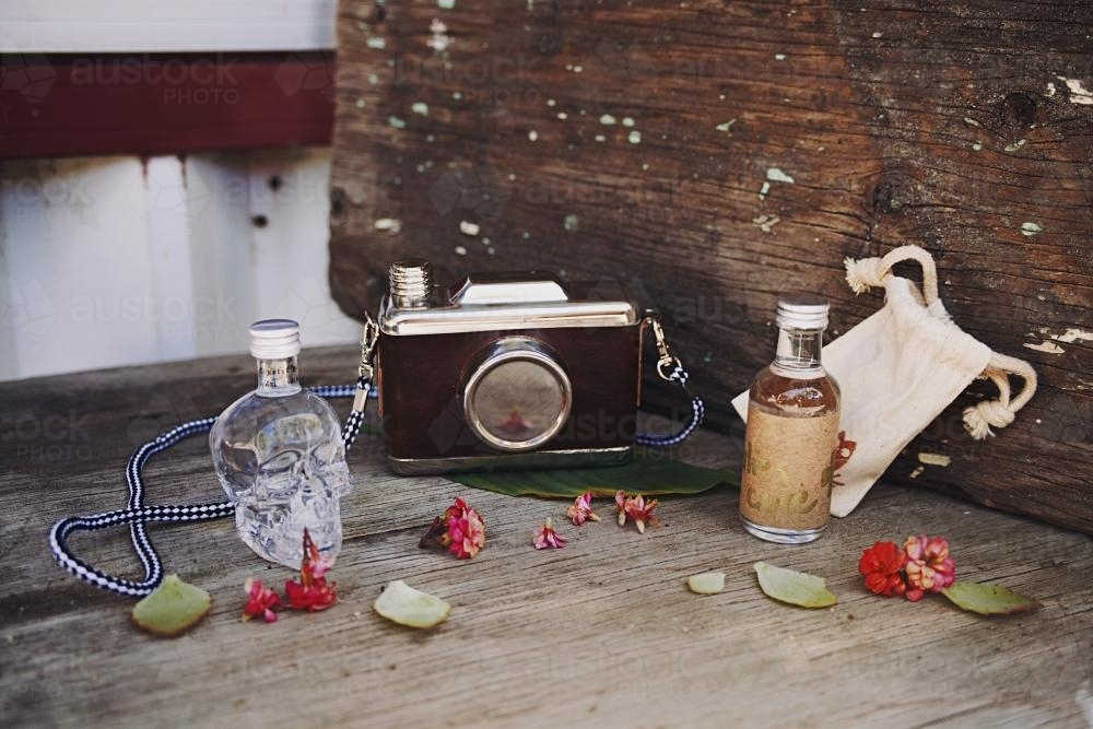 small alcohol bottles and camera flash on a table - Australian Stock Image