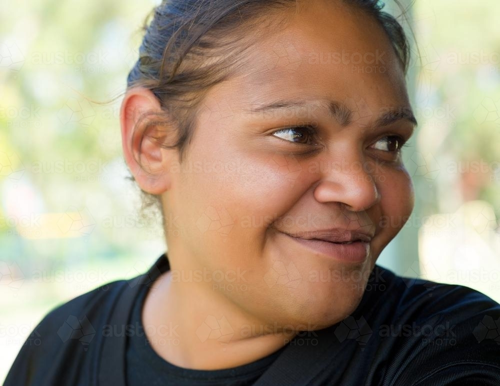 Smiling Aboriginal Woman on a Green Background - Australian Stock Image