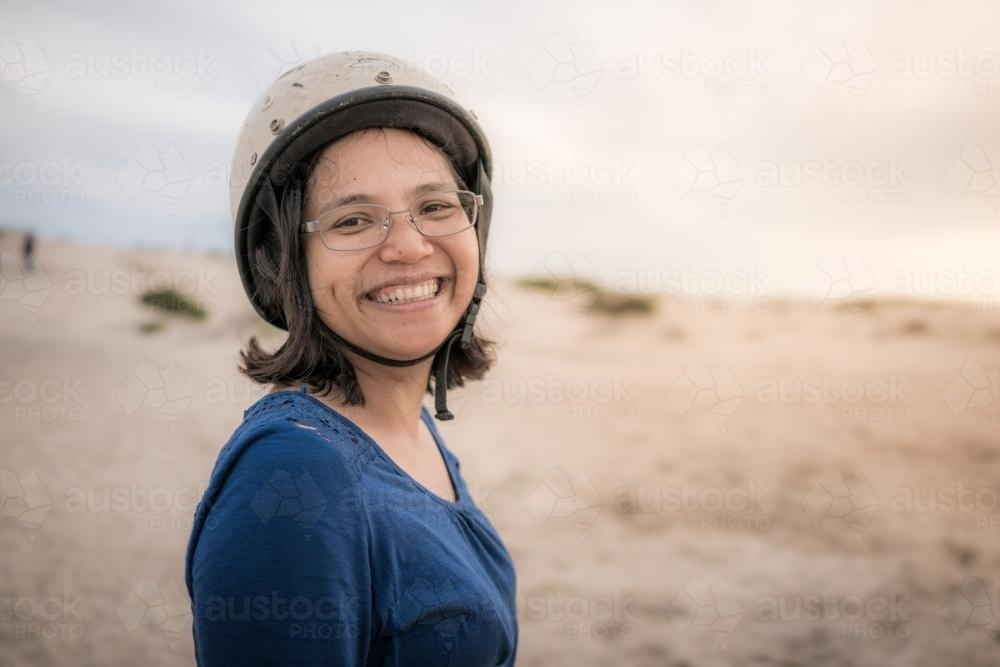 Smiling Asian mother ready to ride camels on beach at sunset - Australian Stock Image